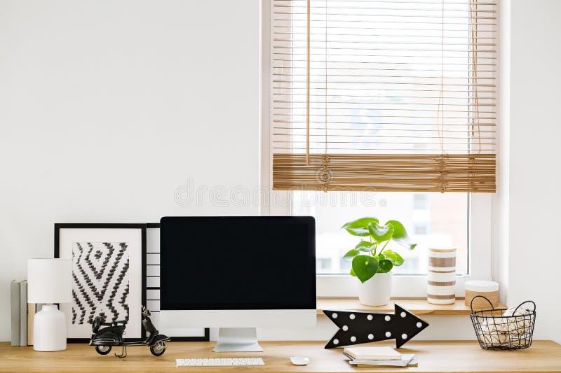 Nahaufnahme auf einem unbedeutenden, weißen Arbeitsplatzinnenraum durch ein Fenster w lizenzfreie stockfotos