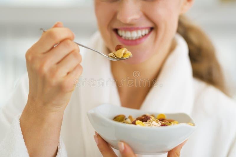 Nahaufnahme auf glücklicher Frau im Bademantel, der gesundes frühstückt lizenzfreie stockfotos