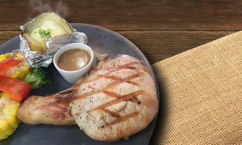 Nahaufnahme auf Grilled Schweinekotelettsteak mit heißer frischer Kartoffel backen lizenzfreie stockbilder