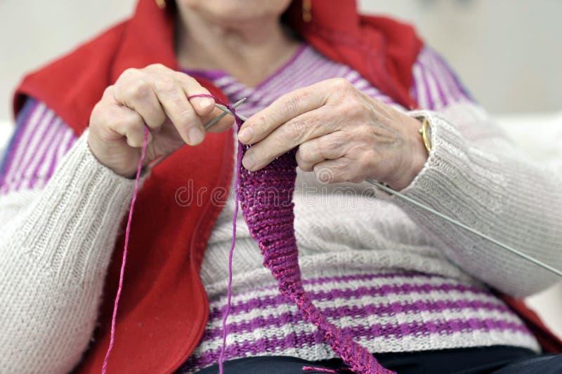 Nahaufnahme auf Händen des Strickens der älteren Frau lizenzfreies stockfoto