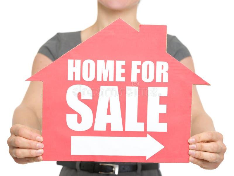 Nahaufnahme auf Haus für Verkauf kennzeichnen innen weibliche Hand lizenzfreie stockfotografie
