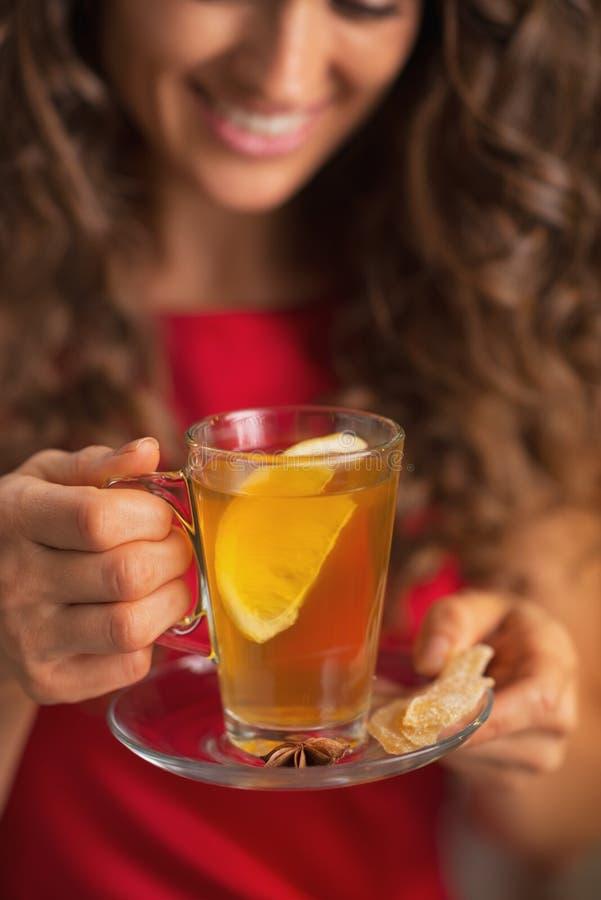 Nahaufnahme auf Ingwertee mit Zitrone in der Hand der jungen Frau lizenzfreie stockfotos