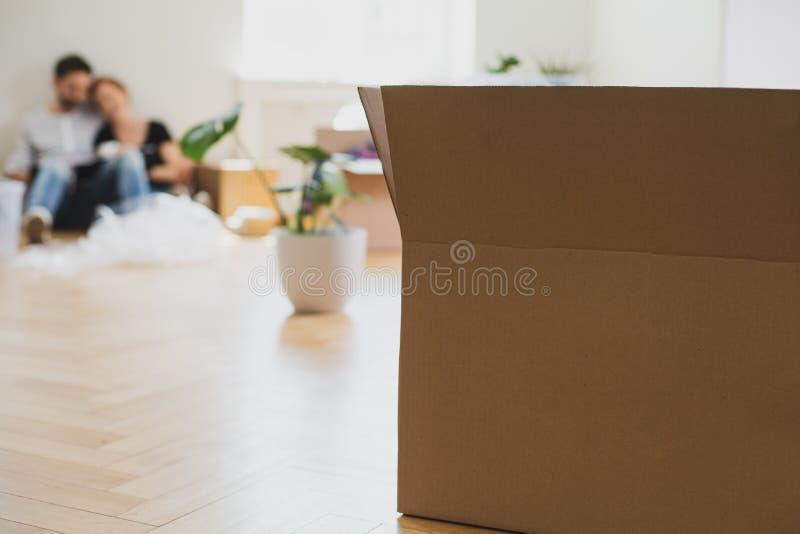 Nahaufnahme auf Kartonkasten auf dem Boden während der Verpackung Anlage und Paare im Hintergrund stockfoto