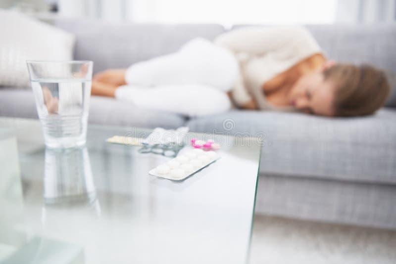 Nahaufnahme auf Medizin auf Tabelle und fühlender schlechter Frau im Hintergrund lizenzfreie stockfotos