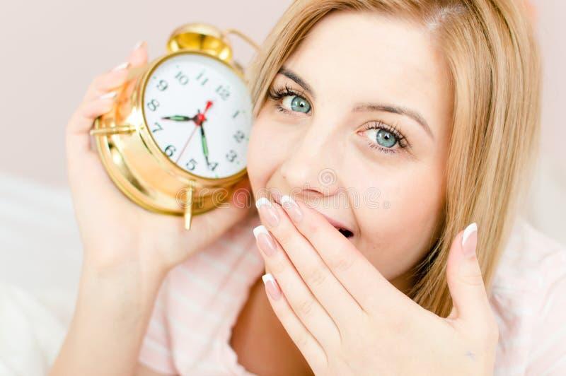 Nahaufnahme auf süßem nettem reizend blondem Mädchen der jungen Frau mit schläfrigem Gesicht und einem Wecker in der Hand lizenzfreie stockfotografie