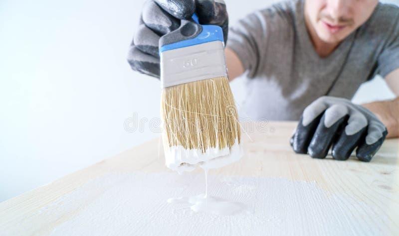 Nahaufnahme: Bürste mit Farbe auf einem Holztisch und einem Glas mit Kopienraum stockfotografie