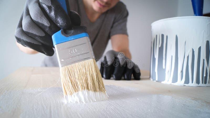 Nahaufnahme: Bürste mit weißer Farbe auf einem Holztisch und einem Glas mit Farbe stockbild