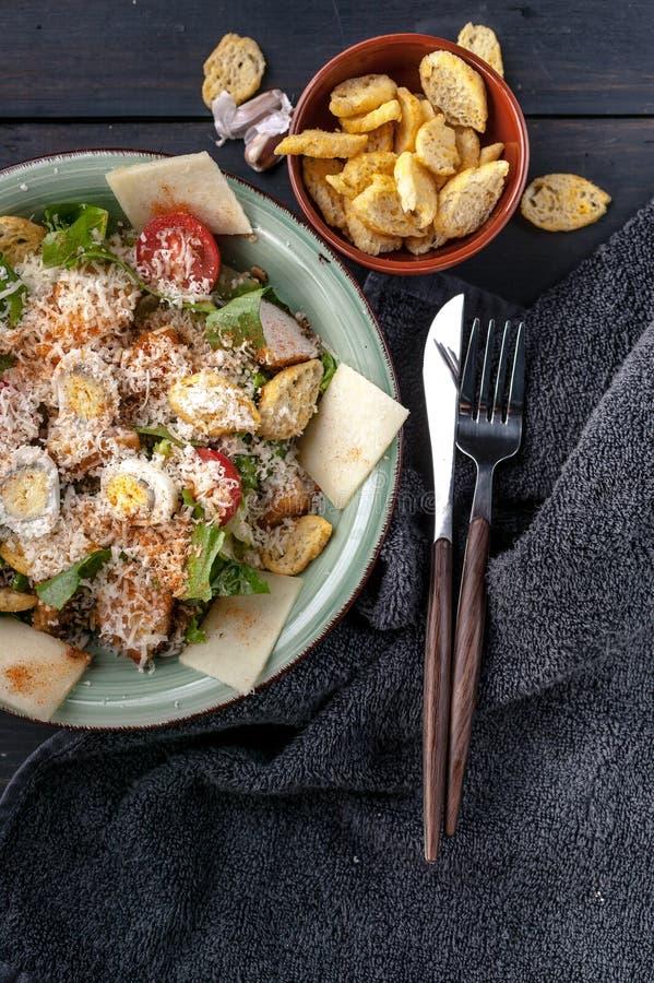 Nahaufnahme-Caesar-Salat mit Wachtelei, gebratenem Huhn, Parmesankäseparmesankäse und Croutons auf einem dunklen rustikalen Hinte lizenzfreie stockfotos