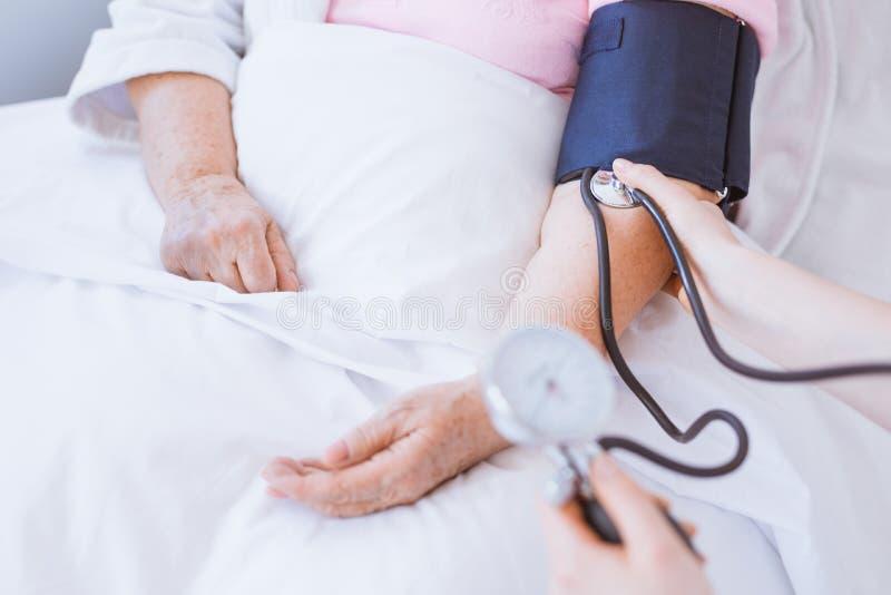 Nahaufnahme der älteren Frau mit Blutdruckmonitor auf Arm stockbilder