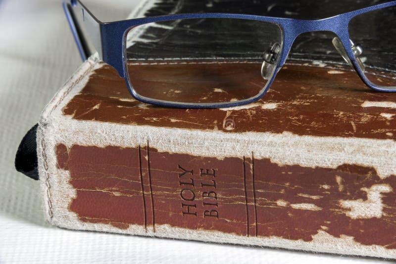 Nahaufnahme der abgenutzten ledernen Bibel mit den Gläsern, die auf die Oberseite stillstehen stockbild