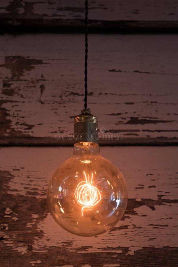 Nahaufnahme der alten Glühlampe, abgenutzter hölzerner Hintergrund lizenzfreies stockfoto