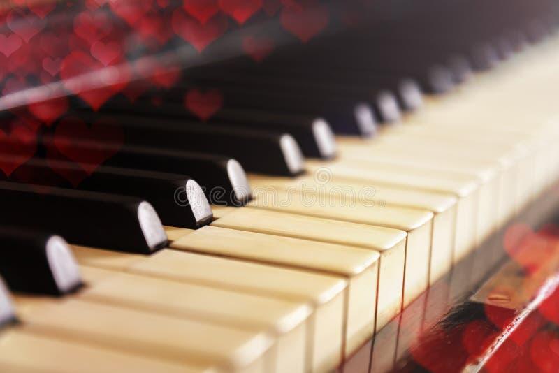 Nahaufnahme der alten Klaviertastatur, selektiver Fokus, weiches Tonen Valentinstaghintergrund, Weinleseklavier und bokeh Herzen stockfotos