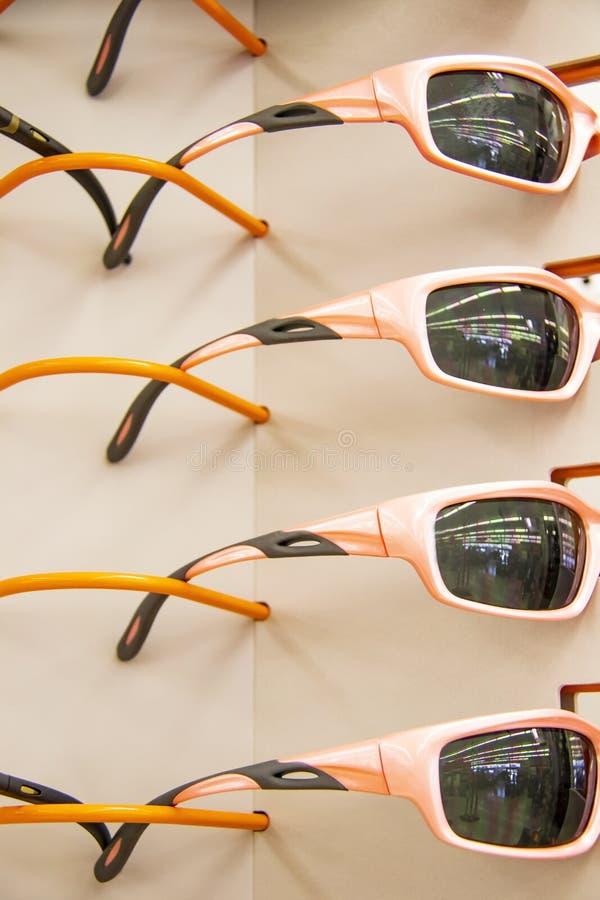 Nahaufnahme der Anzeige der orange-rosa Sportsonnenbrille mit identischen refletctions in den Linsen lizenzfreie stockfotos