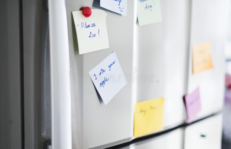 Nahaufnahme der Anzeigenpapieranmerkung über Kühlschranktür stockfotografie