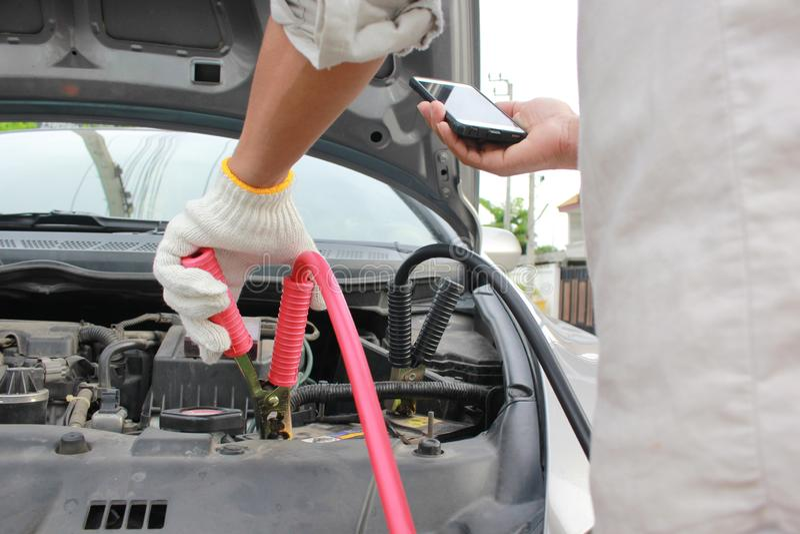 Nahaufnahme der Aufladungsautomobil entladenen Batterie und des Mannes, die zum Automechanikerservice nennen stockfotografie