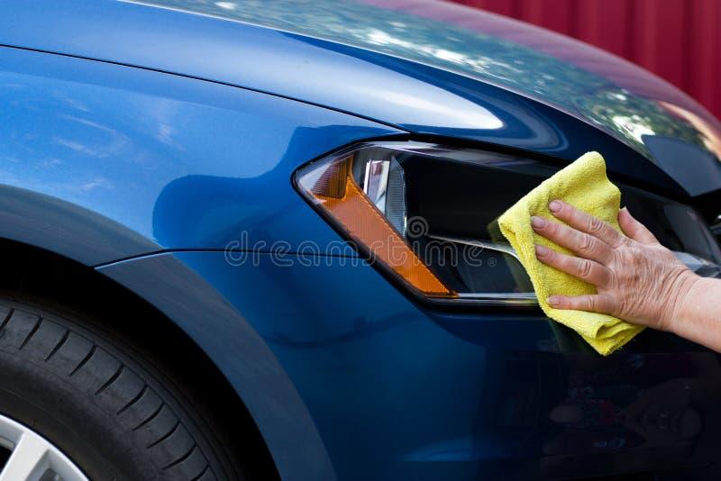 Nahaufnahme der blauen Autoreinigung mit gelbem microfiber Stoff durch wom stockfoto