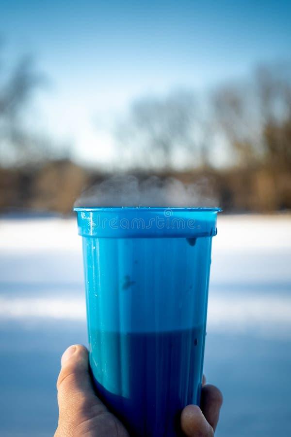Nahaufnahme der blauen Plastikschale mit heißem Wein und dem Dampf, die in der Hand hält lizenzfreie stockfotos