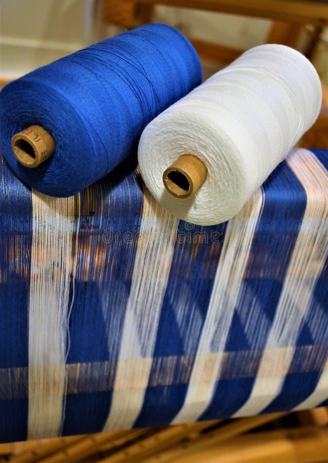 Nahaufnahme der blauen und weißen gestreiften Verzerrung mit zwei Baumwollgarnen benutzt in der Verzerrung spinnen Handweaving ge stockfotos