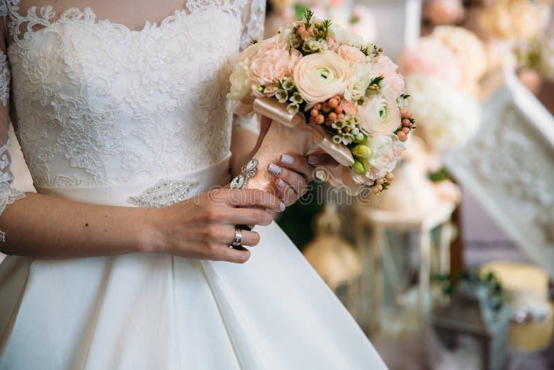 Nahaufnahme der Braut übergibt das Halten des schönen Hochzeitsblumenstraußes mit den weißen und rosa Rosen Konzept von floristic stockfotografie