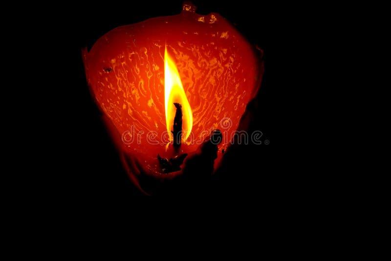 Nahaufnahme der brennenden Kerze hell lokalisiert auf schwarzer dunkler Flamme des Hintergrundes einer am Nachtmakro stockfoto