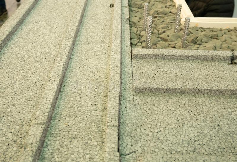 Nahaufnahme der errichtenden Wand mit isolierendem Styroschaum, konkretem Zement und kleinen Steinen lizenzfreie stockfotos