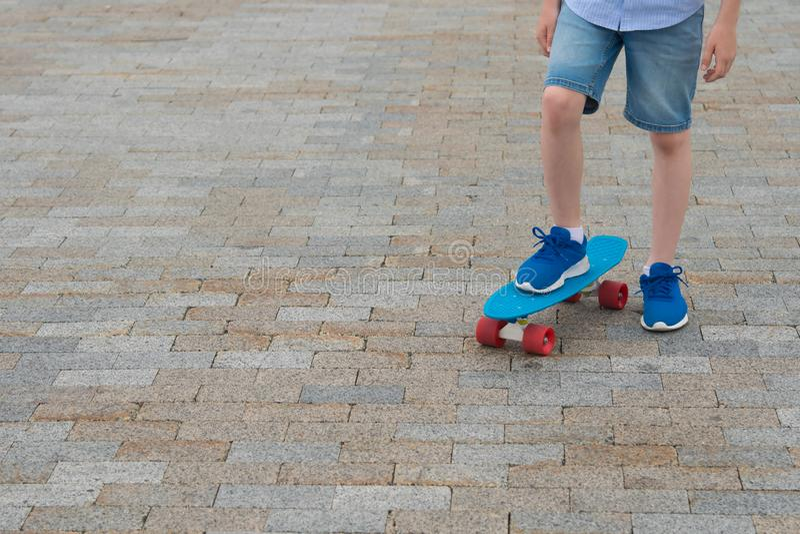Nahaufnahme der Füße einer Jungenstellung auf Sport verschalen in den blauen Turnschuhen, vor dem hintergrund einer Steinstraß lizenzfreie stockbilder