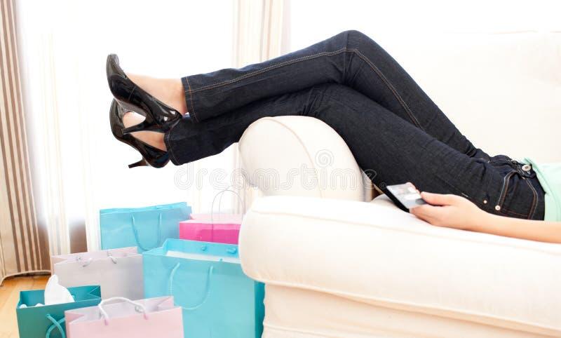 Nahaufnahme der Fahrwerkbeine einer Frau, die auf einem Sofa liegt stockbild