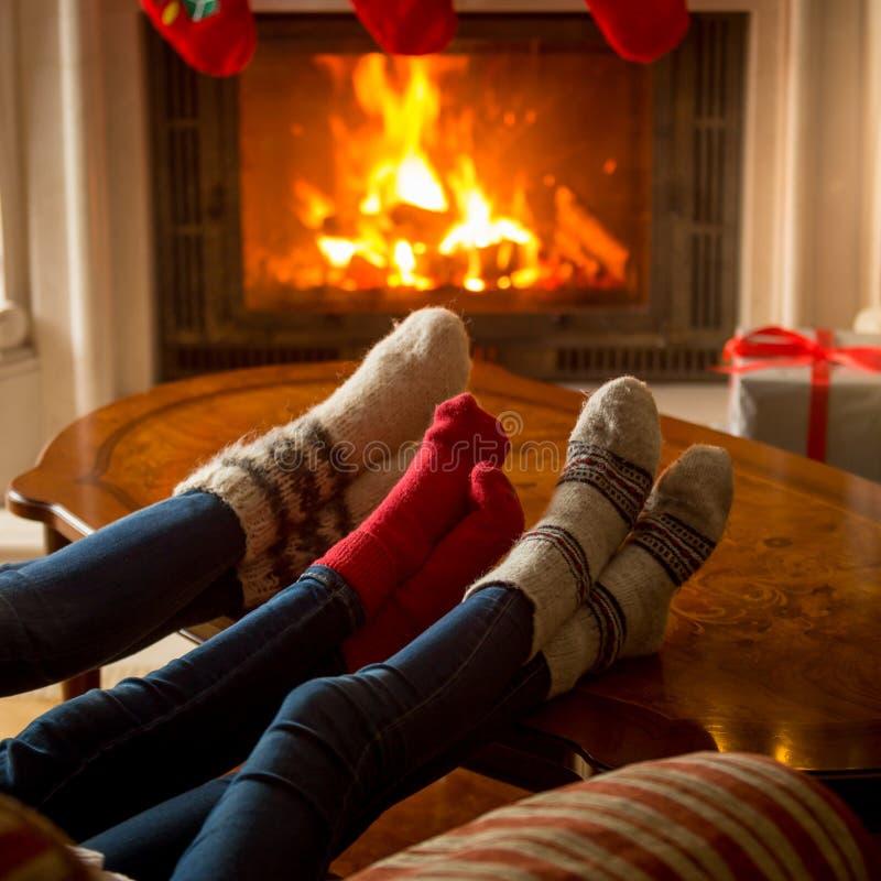 Nahaufnahme der Familie in den gestrickten woolen Socken, die an brennender Tanne sich wärmen lizenzfreie stockfotos