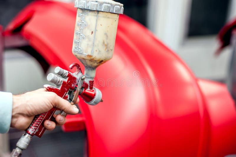Nahaufnahme der Farbspritzpistole mit der roten Farbe, die ein Auto malt stockbild
