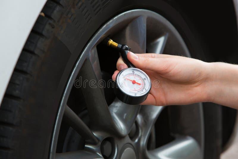 Nahaufnahme der Frau Auto-Reifen-Druck mit Messgerät überprüfend lizenzfreie stockbilder