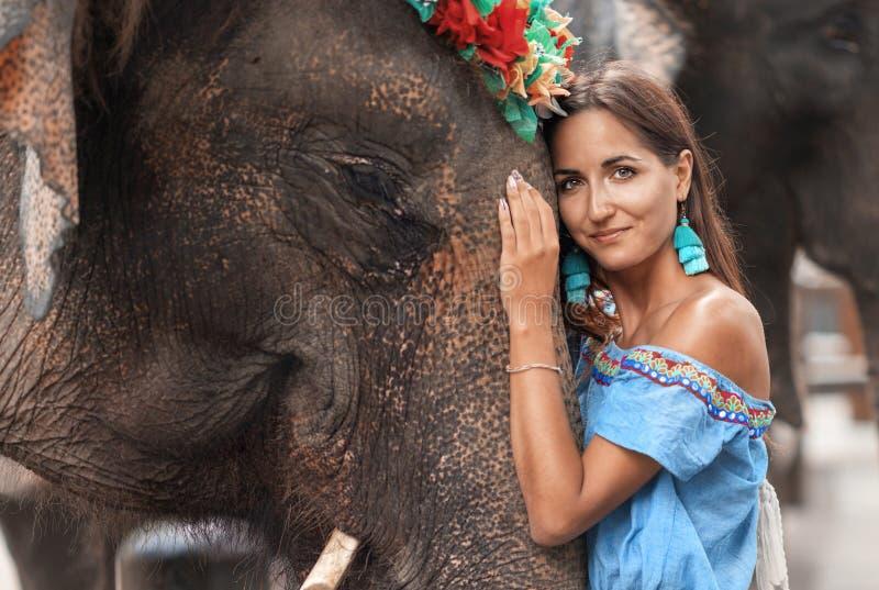 Nahaufnahme der Frau, die den Kopf des Elefanten umarmt lizenzfreie stockfotos