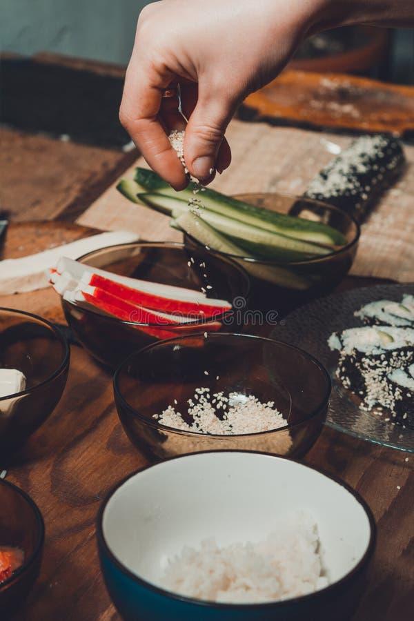 Nahaufnahme der Frauen Handin einem Restaurant besprühen Öl des indischen Sesams während der Vorbereitung von Sushi stockfoto
