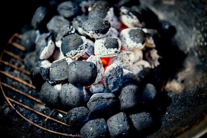Nahaufnahme der glühenden Kohle im Metallgrill am Sommertag im Garten stockfotografie