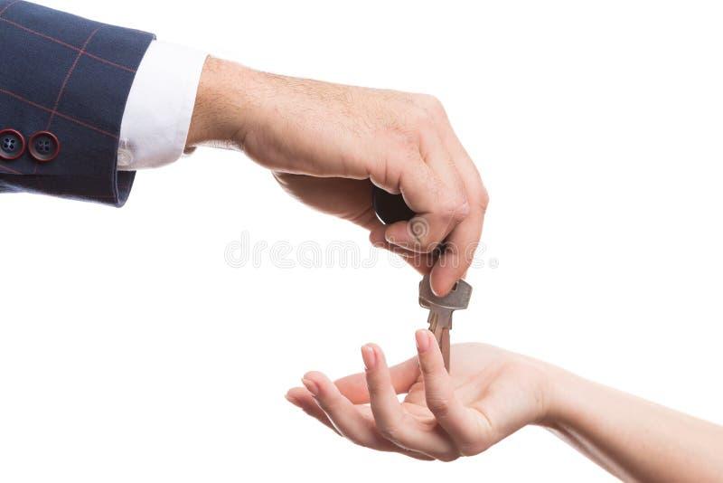 Nahaufnahme der Grundstücksmaklerhand Schlüssel gebend lizenzfreie stockfotos