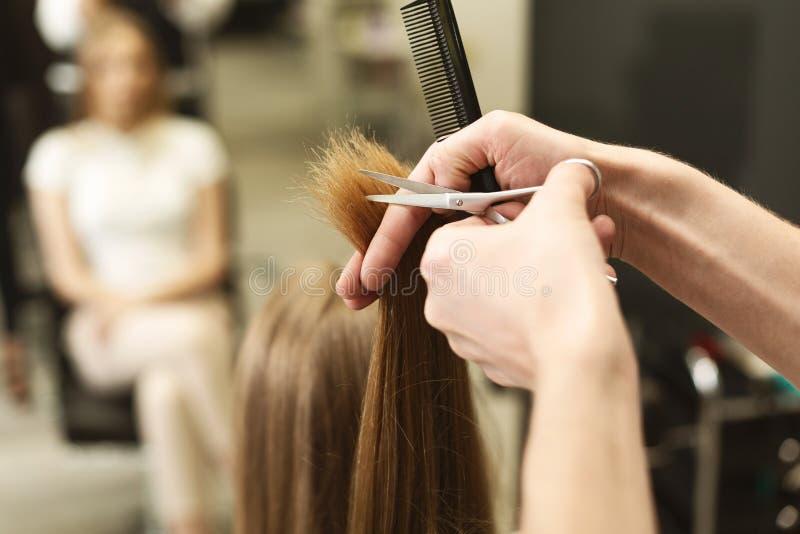 Nahaufnahme der Hände des Friseurs, die aufgeteilte Enden auf weiblichem Haar im Salon trimmen stockbild