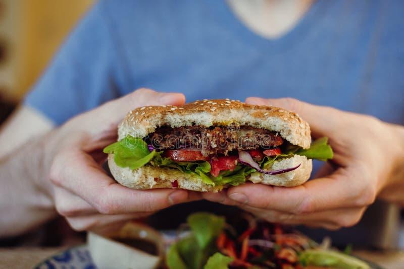 Nahaufnahme der Hände des Mannes, die Kichererbse des strengen Vegetariers und Bohnenburger mit neuen Grüns halten lizenzfreies stockfoto