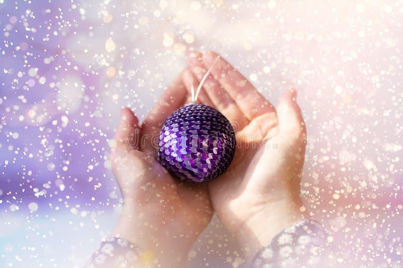 Nahaufnahme der Hände eines jungen Mädchens, die einen Weihnachtsball halten Glänzende Paillette auf einem Weihnachtsball lizenzfreie stockfotografie