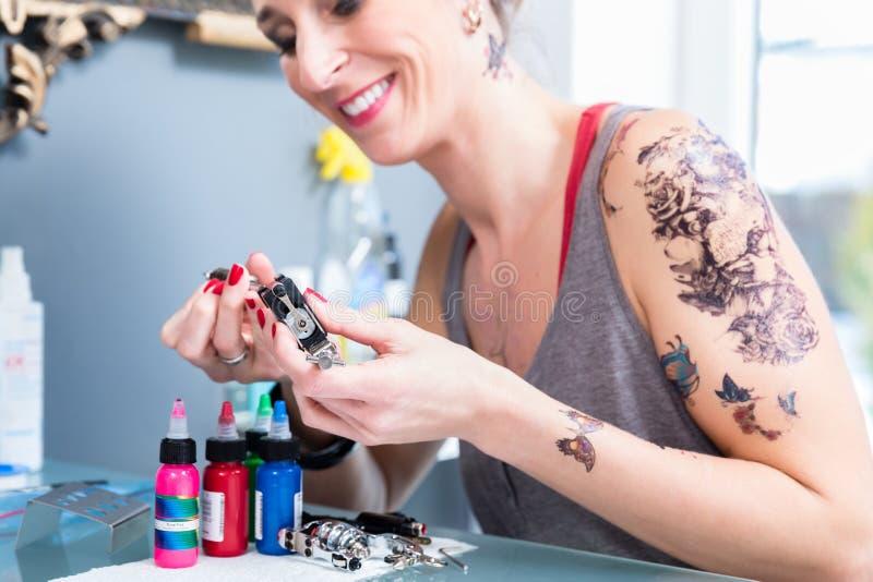 Nahaufnahme der Hände eines weiblichen Künstlers, der eine Berufstätowierungsmaschine vorbereitet stockbild