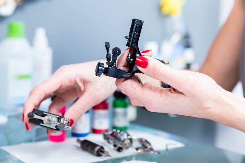 Nahaufnahme der Hände eines weiblichen Künstlers, der eine Berufstätowierungsmaschine vorbereitet stockfotografie