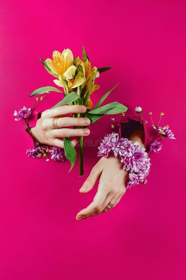 Nahaufnahme der Hände der Frau durch heftige Papierwerte gelbe Alstroemerias und Chrysanthemenarmband stockfoto
