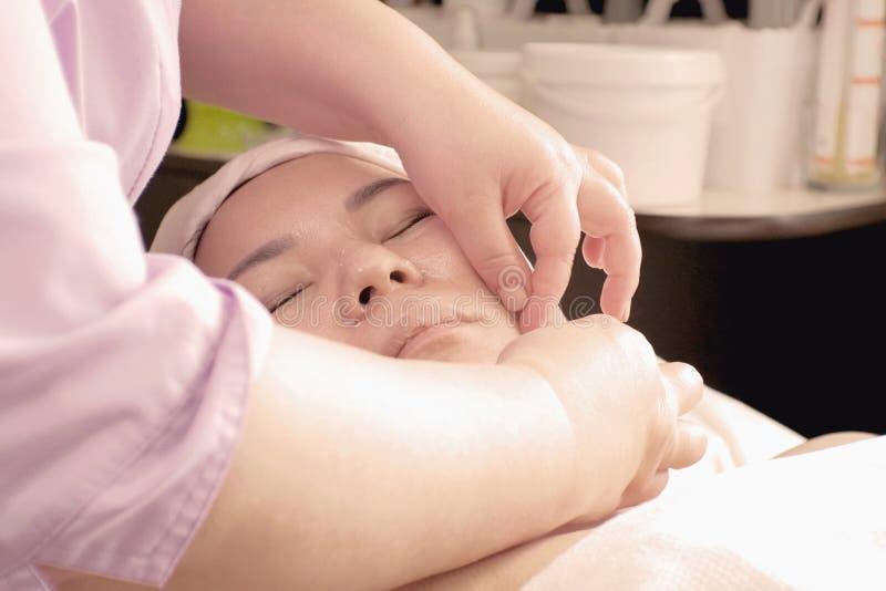 Nahaufnahme der Hände der Frauen, die asiatisches Mädchen des Acupressure in einem Schönheitssalon tun Verfahren für die Gesundhe stockfoto