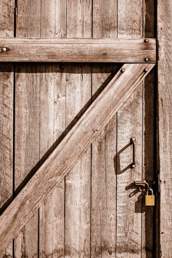Nahaufnahme der hölzernen Tür zu einem alten weggelaufenen Haus schloss mit flachem Gold stockfotos