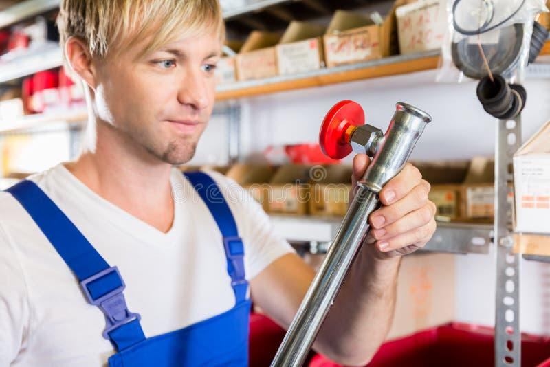 Nahaufnahme der Hand einer Arbeitskraft, die ein metallisches Rohr während der Qualitätskontrolle hält stockbild
