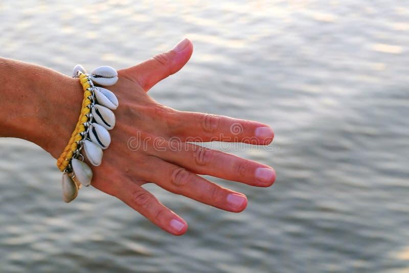 Nahaufnahme der Hand eines leichten Mädchens mit einem Armband hergestellt von den Muscheln auf dem Hintergrund des Wassers lizenzfreies stockfoto