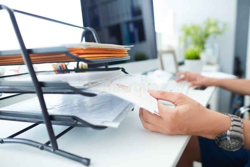 Nahaufnahme der Hand eines Mannes, die Dateien von den Büroregalen zieht lizenzfreies stockbild