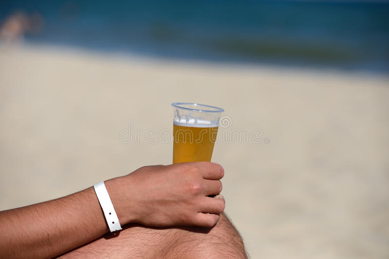 Nahaufnahme der Hand eines Mannes mit einem Auffrischungsbier auf dem Strand stockfotografie