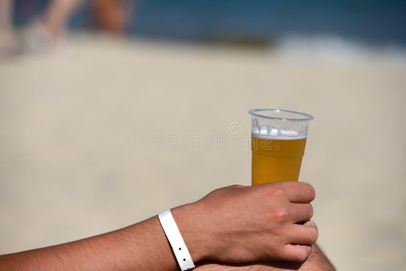 Nahaufnahme der Hand eines Mannes mit einem Auffrischungsbier auf dem Strand stockfoto