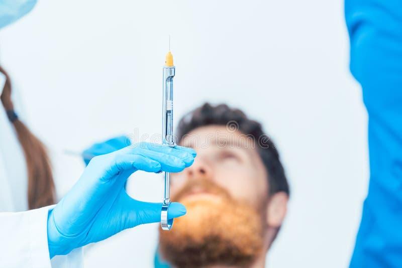 Nahaufnahme der Hand eines weiblichen Zahnarztes, der ein zahnmedizinisches Betäubungsmittel hält lizenzfreie stockfotografie