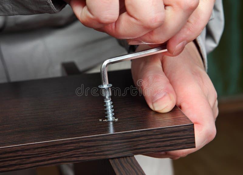 Nahaufnahme der Hand mit Allen-Schlüssel, zusammenbauende Möbel stockfoto