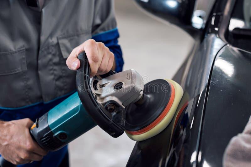 Nahaufnahme der Handarbeitskraft, die Poliermittel verwendet, um eine schwarze Fahrzeugkarosserie in der Werkstatt zu polieren lizenzfreie stockbilder